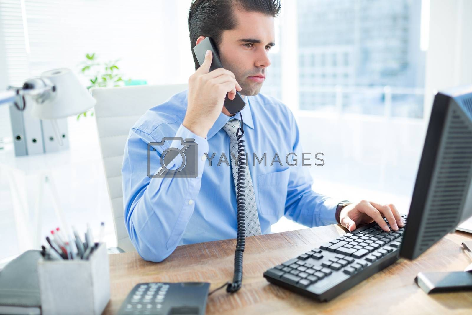 Royalty free image of Businessman using computer and phoning  by Wavebreakmedia