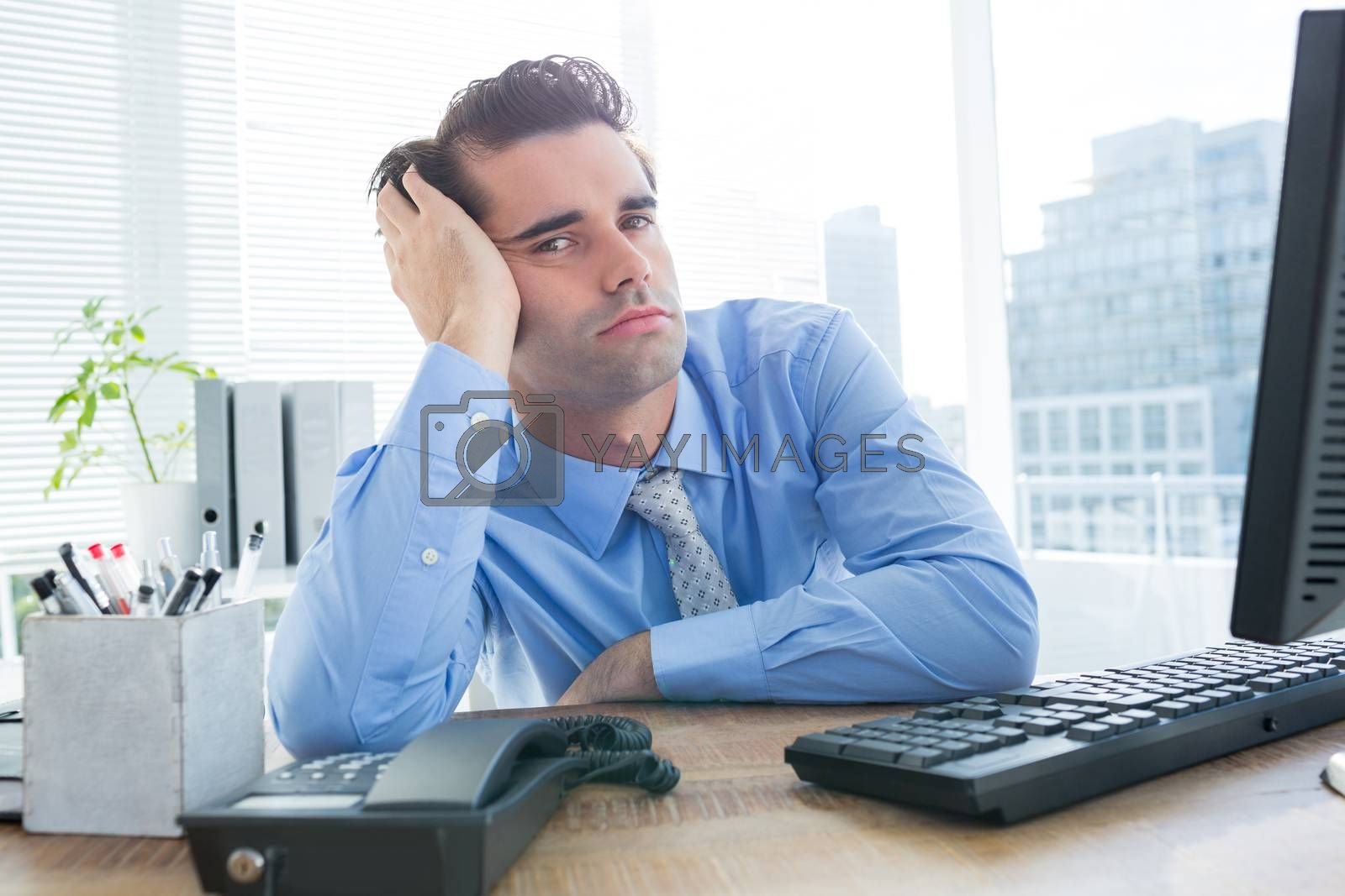 Royalty free image of Businessman looking at camera in office by Wavebreakmedia