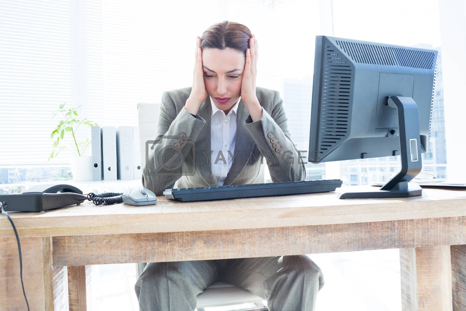 Royalty free image of Upset business woman with head in hands in front of computer at office by Wavebreakmedia