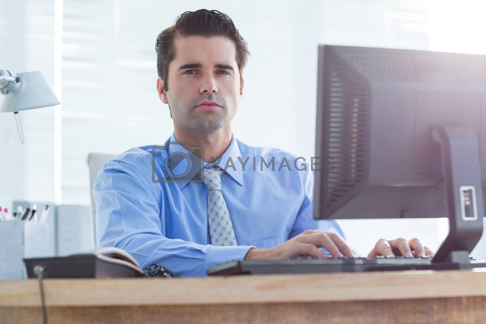 Royalty free image of Serious businessman using computer by Wavebreakmedia