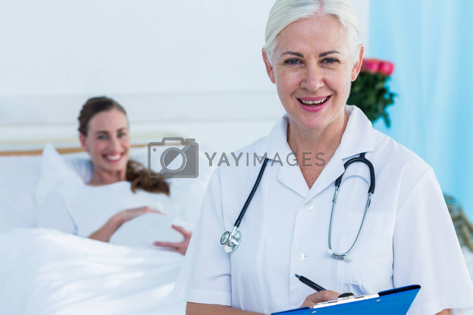 Royalty free image of Female doctor and pregnant woman smiling at camera by Wavebreakmedia