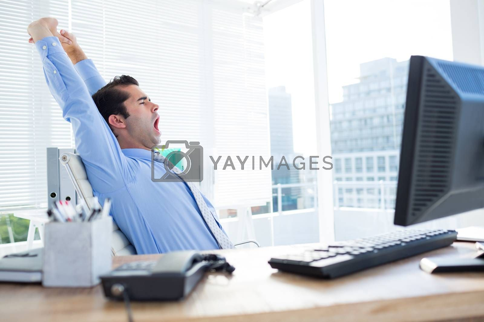 Royalty free image of Businessman yawning and stretching  by Wavebreakmedia