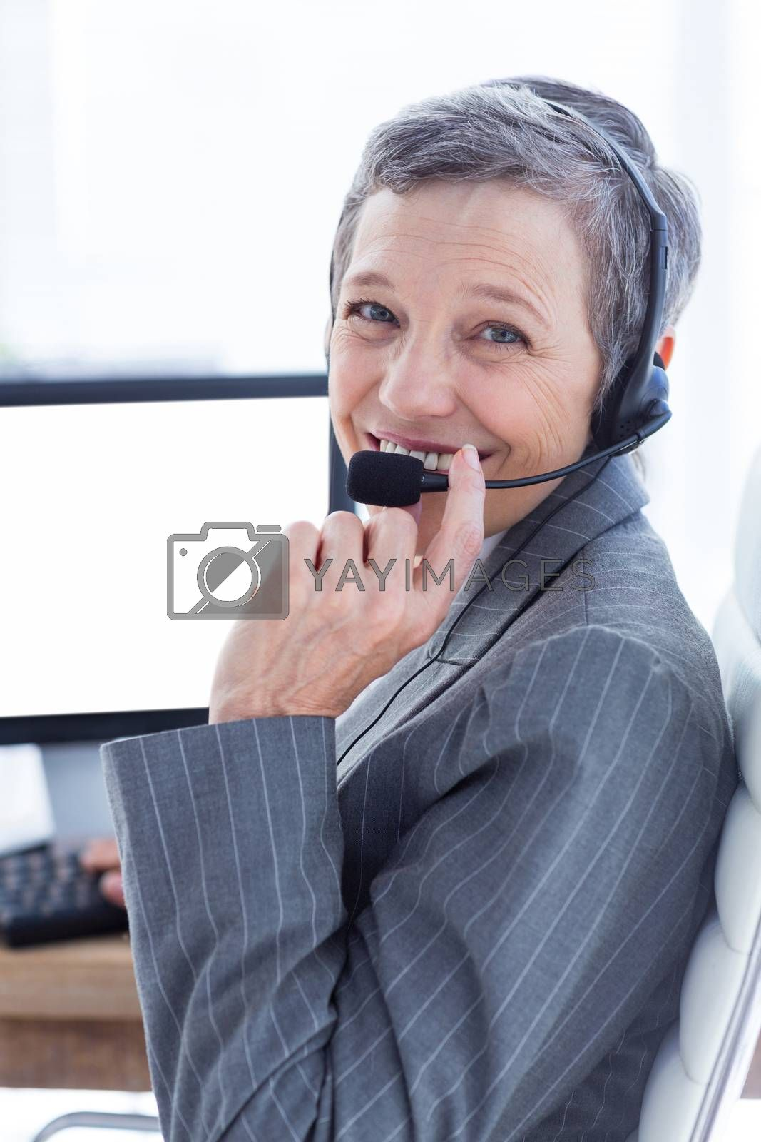 Royalty free image of Smiling businesswoman phoning and using computer  by Wavebreakmedia