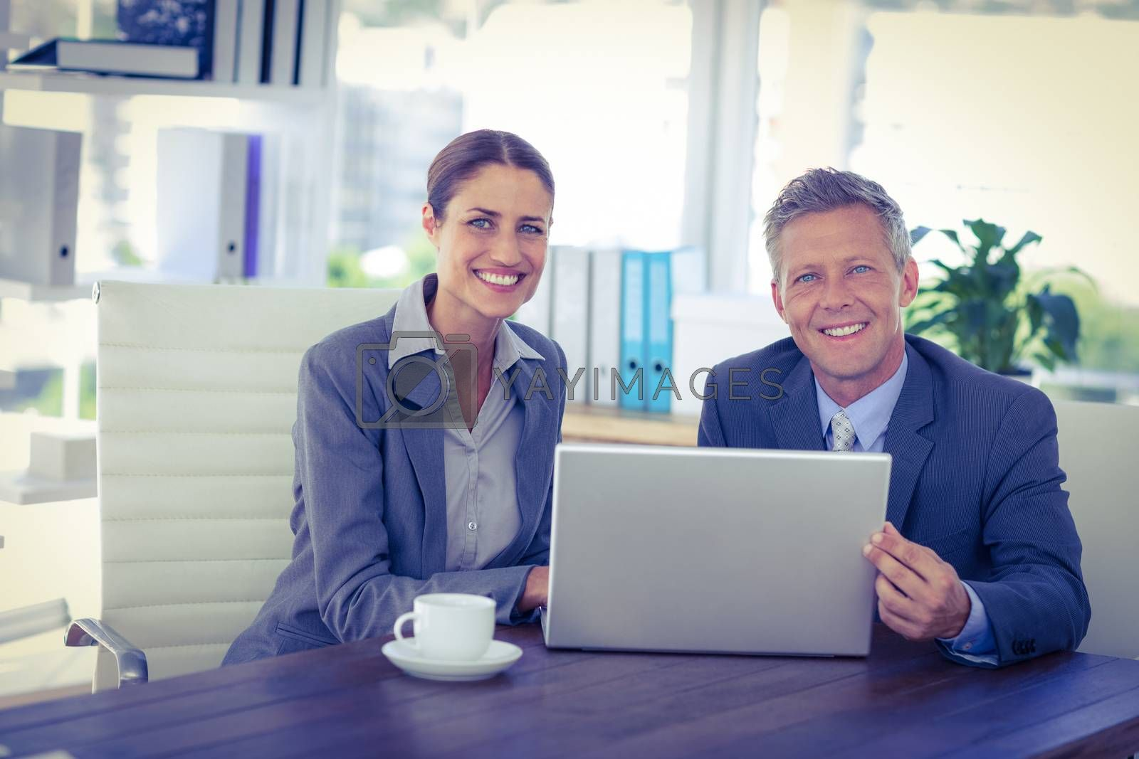 Royalty free image of Business people looking at camera and using laptop  by Wavebreakmedia