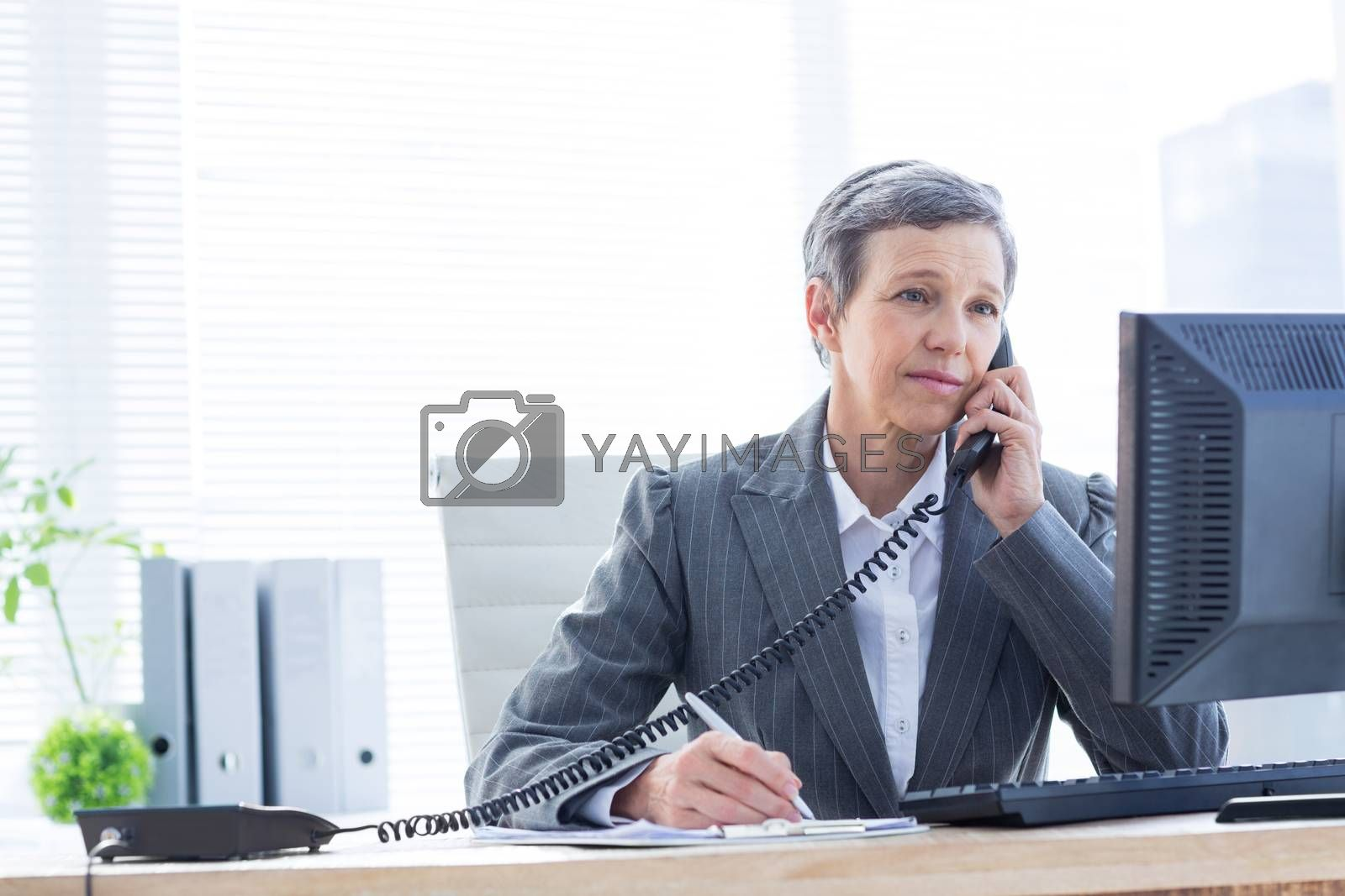 Royalty free image of Smiling businesswoman phoning and writing  by Wavebreakmedia