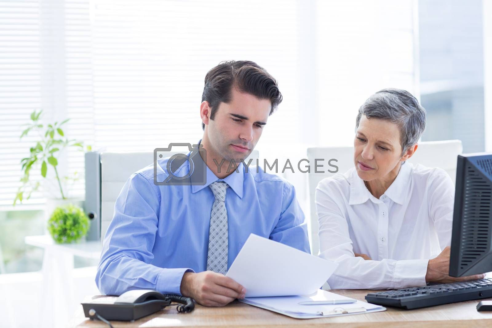 Royalty free image of Two business people looking at a paper while working on computer  by Wavebreakmedia