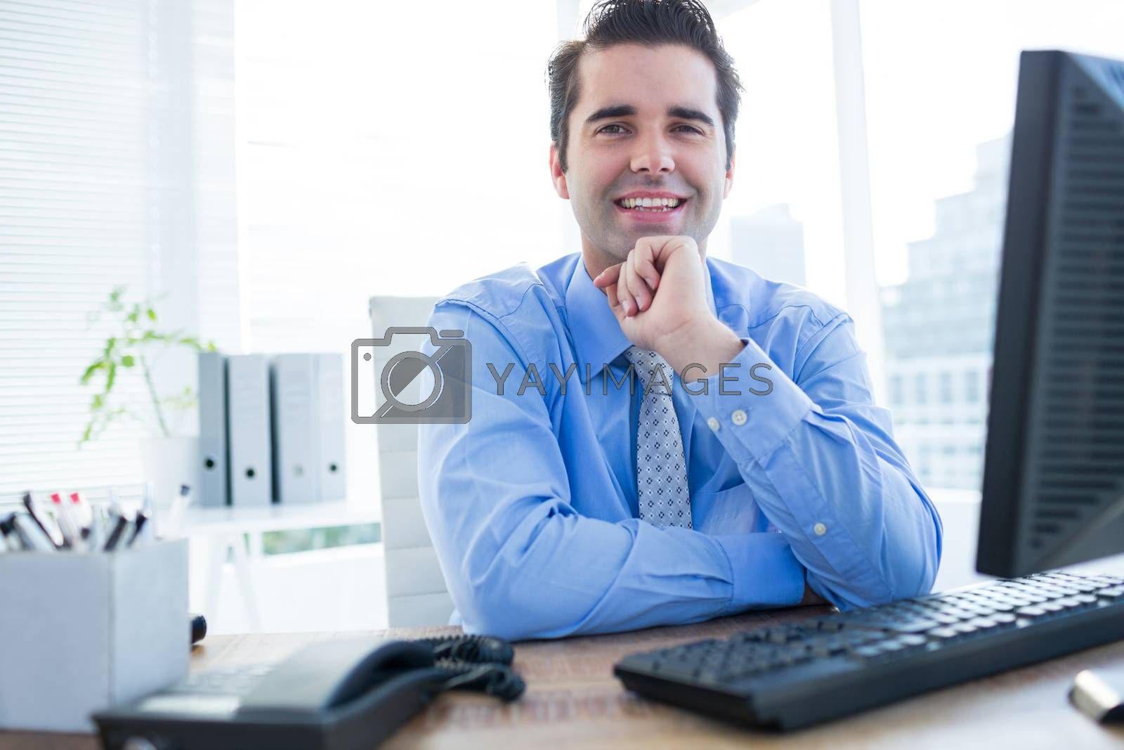 Royalty free image of Cheerful businessman using computer in office by Wavebreakmedia