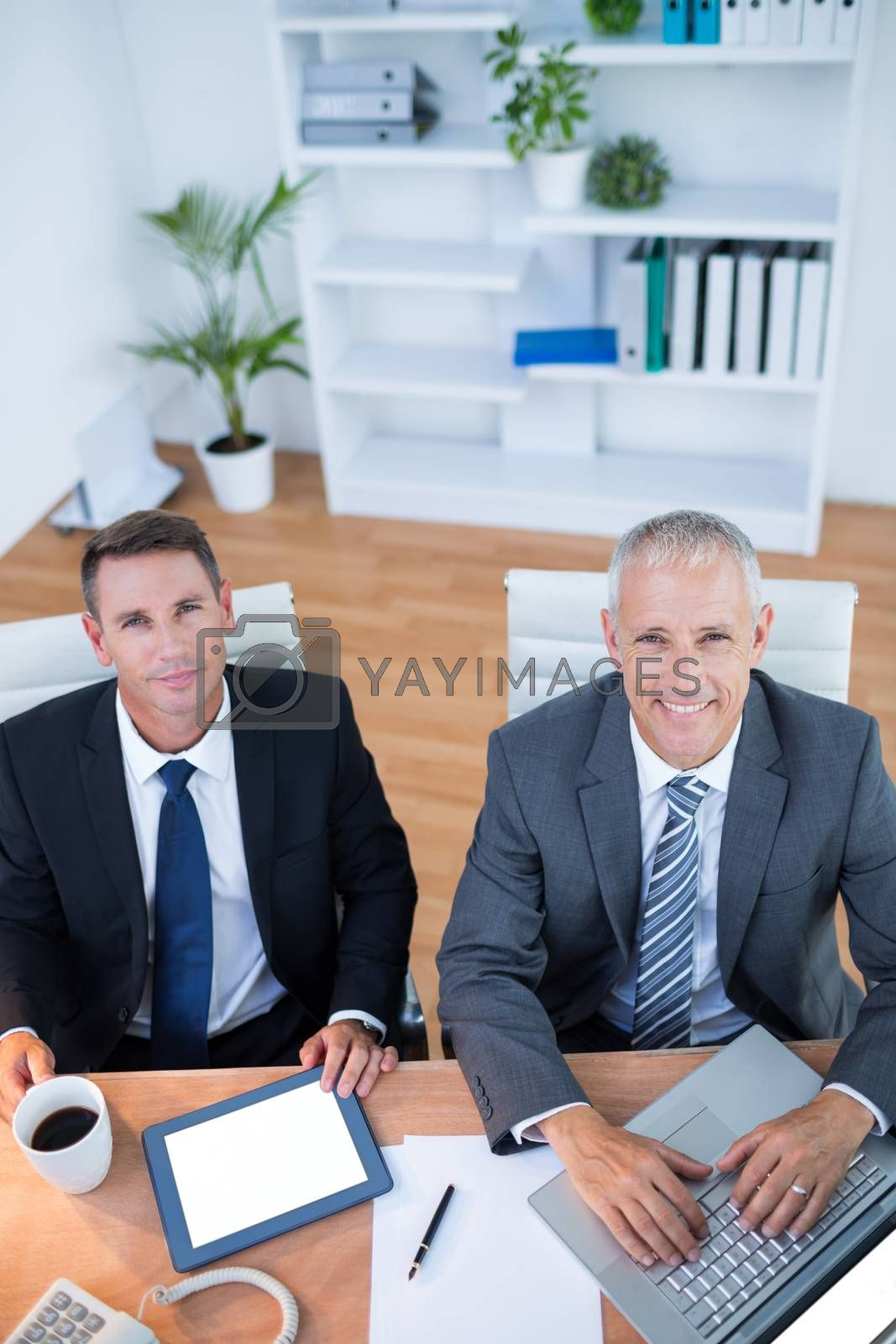Royalty free image of Happy colleagues working together on digital tablet and laptop  by Wavebreakmedia