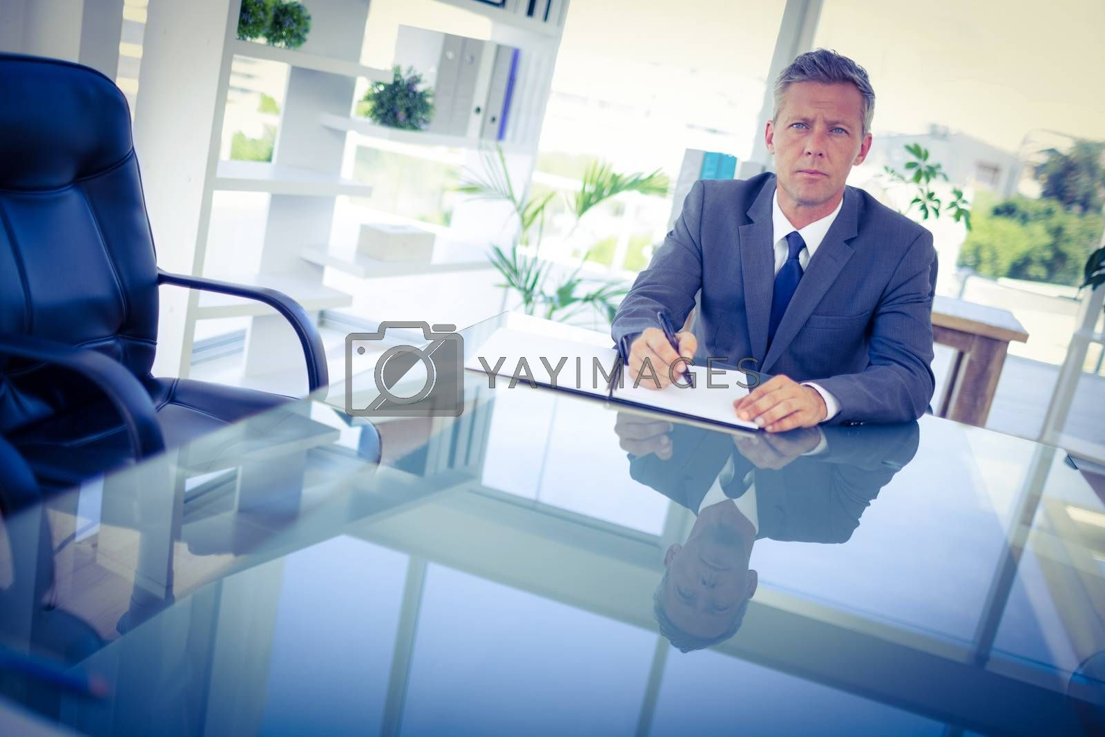 Royalty free image of Businessman writing on clipboard and looking at camera  by Wavebreakmedia