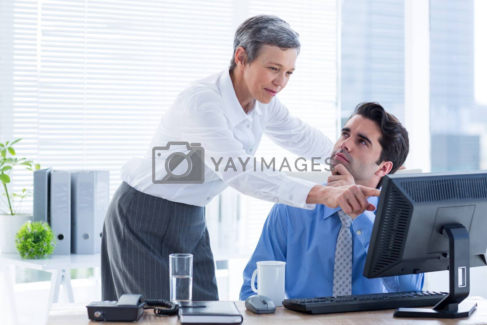 Royalty free image of Serious colleagues working together on computer by Wavebreakmedia