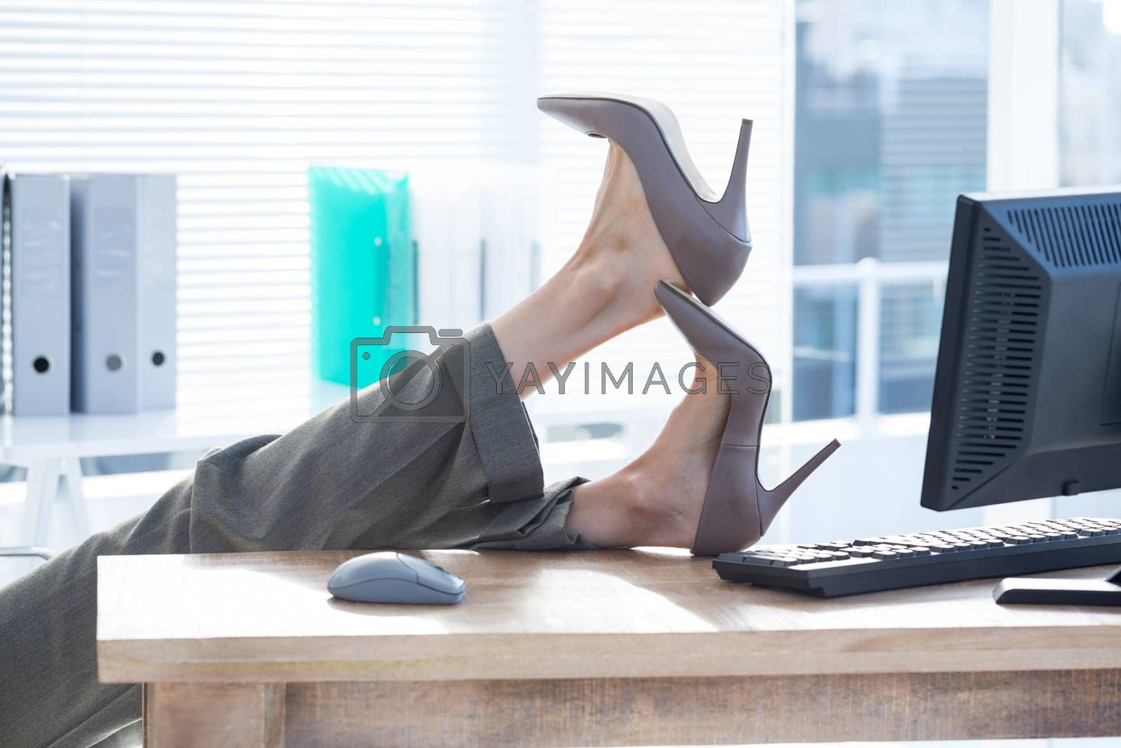 Royalty free image of Businesswoman sitting on swivel chair with feet on desk  by Wavebreakmedia