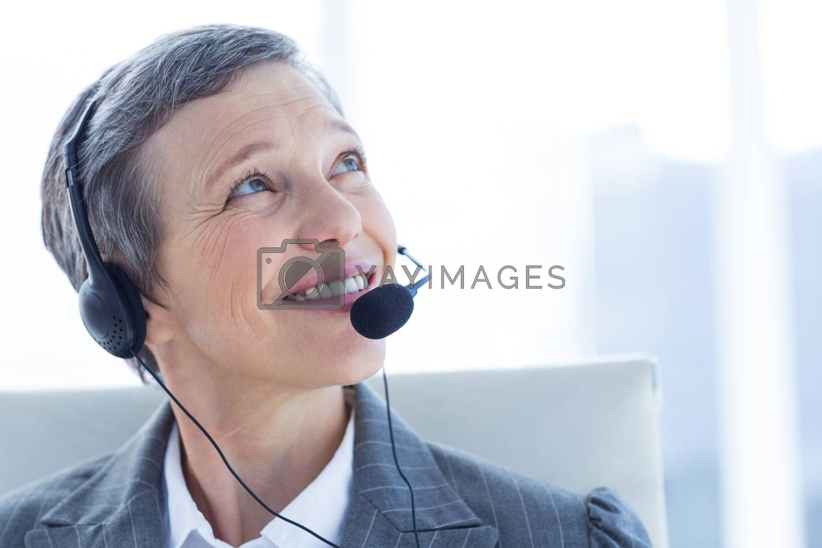 Royalty free image of Smiling businesswoman phoning with headphone by Wavebreakmedia