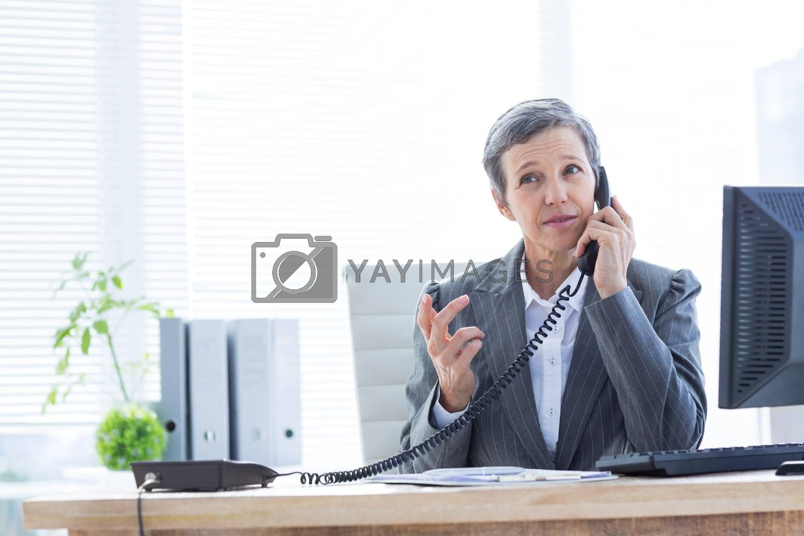 Royalty free image of Serious businesswoman phoning and using computer  by Wavebreakmedia