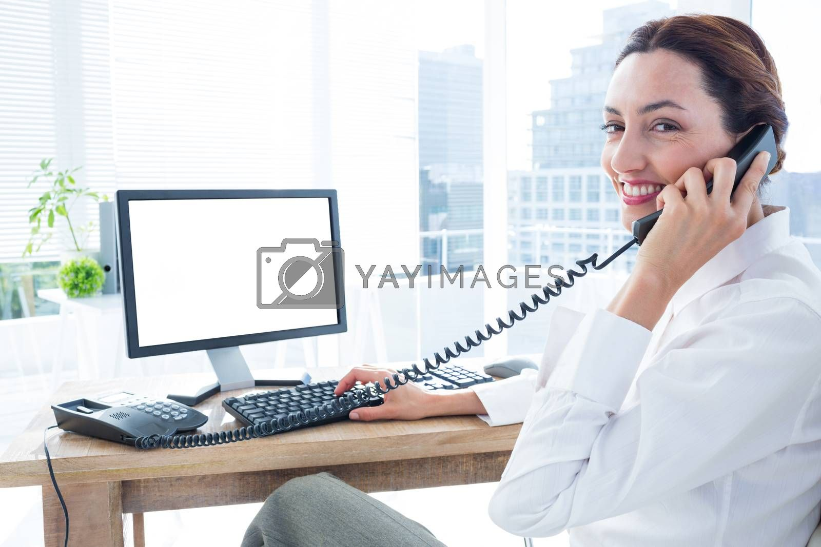 Royalty free image of Smiling businesswoman using computer and phoning  by Wavebreakmedia