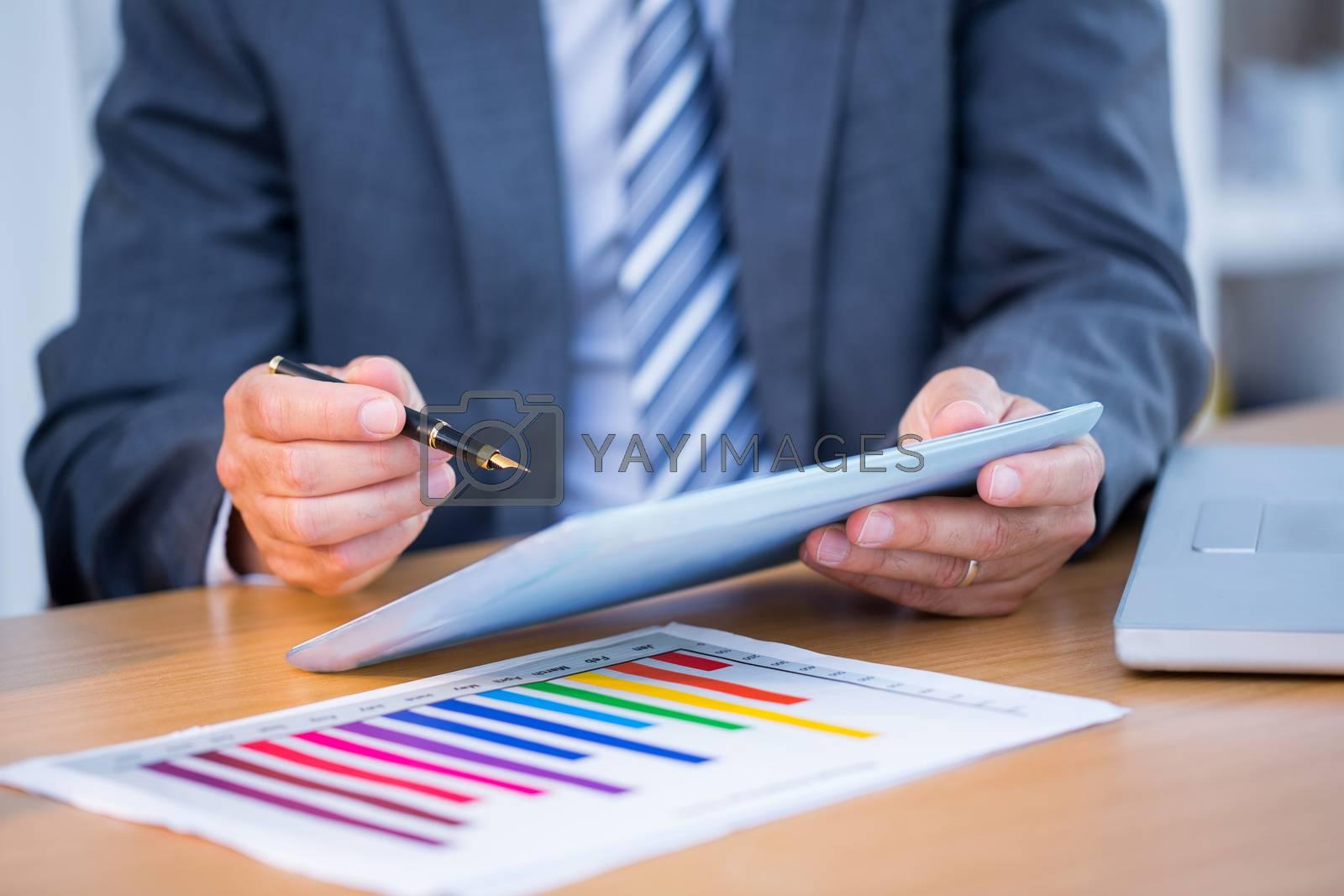 Royalty free image of Businessman working on his digital tablet  by Wavebreakmedia