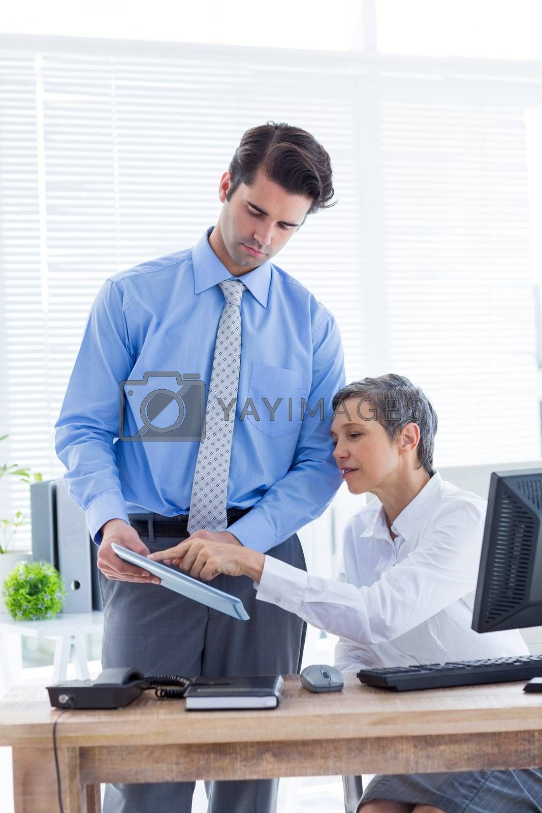 Royalty free image of Serious colleagues working together on folder  by Wavebreakmedia