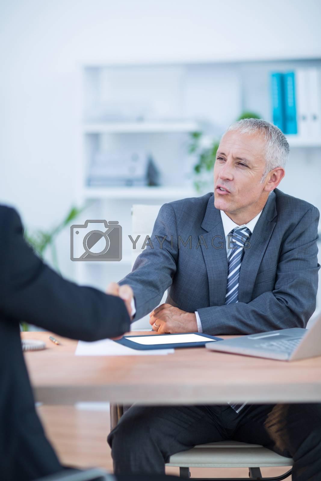 Royalty free image of Happy businessmen shaking hands by Wavebreakmedia
