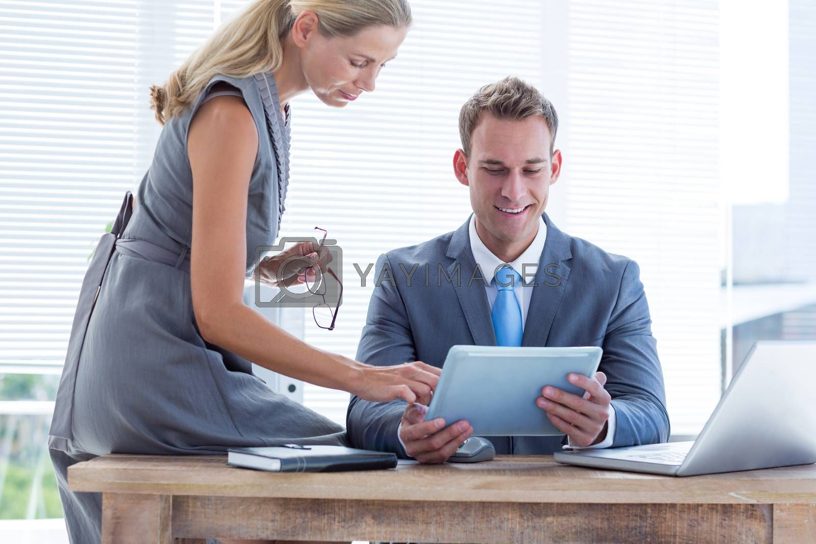 Royalty free image of Happy colleagues working together on tablet by Wavebreakmedia