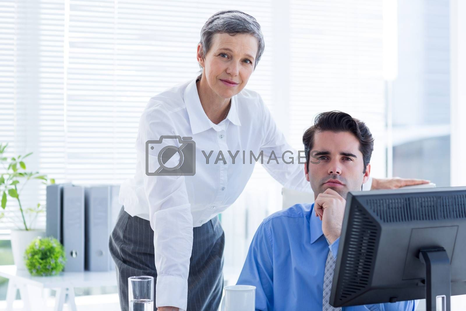 Royalty free image of Business people working together and looking at camera by Wavebreakmedia