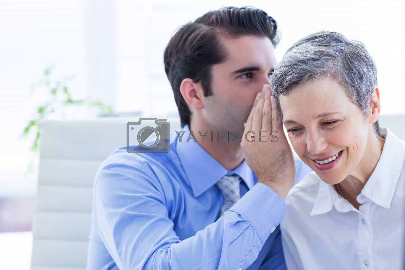 Royalty free image of Two business people looking at a paper while working on folder by Wavebreakmedia
