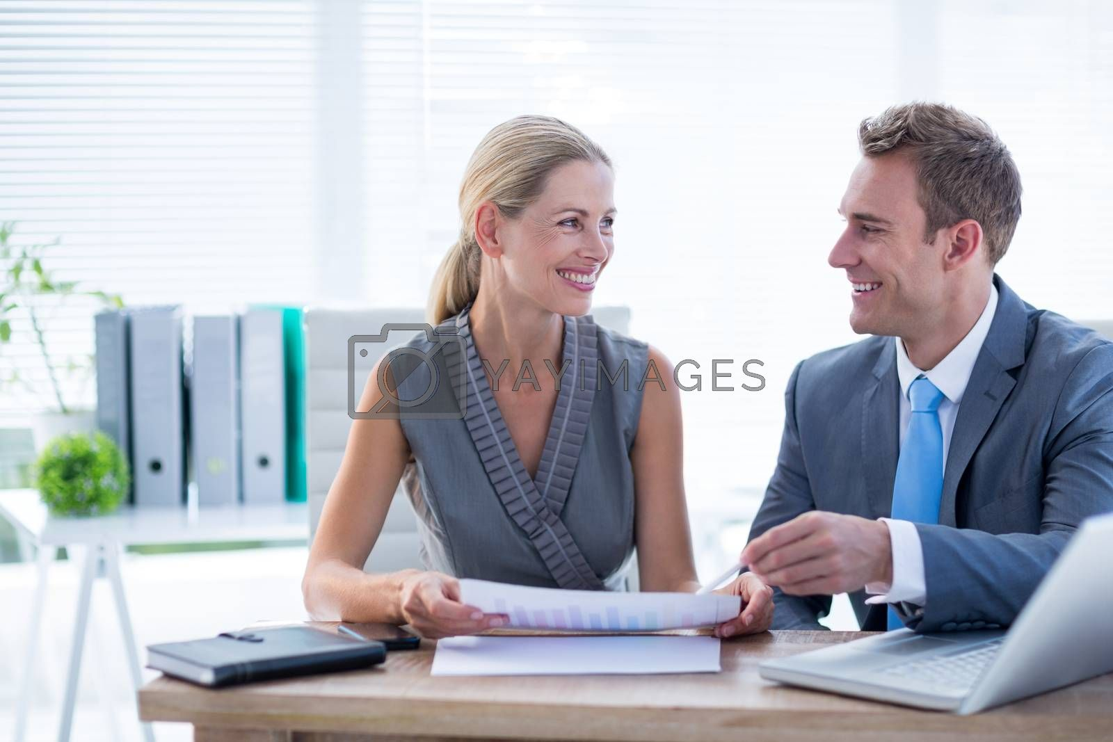 Royalty free image of Happy colleagues working together on laptop and folder by Wavebreakmedia