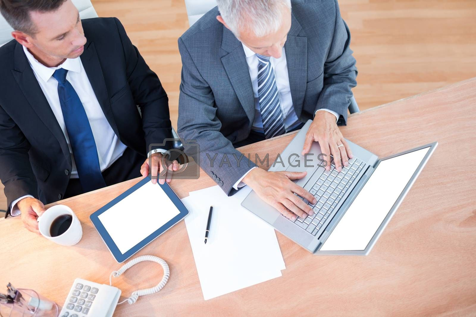 Royalty free image of High view of businessmen working together on laptop by Wavebreakmedia
