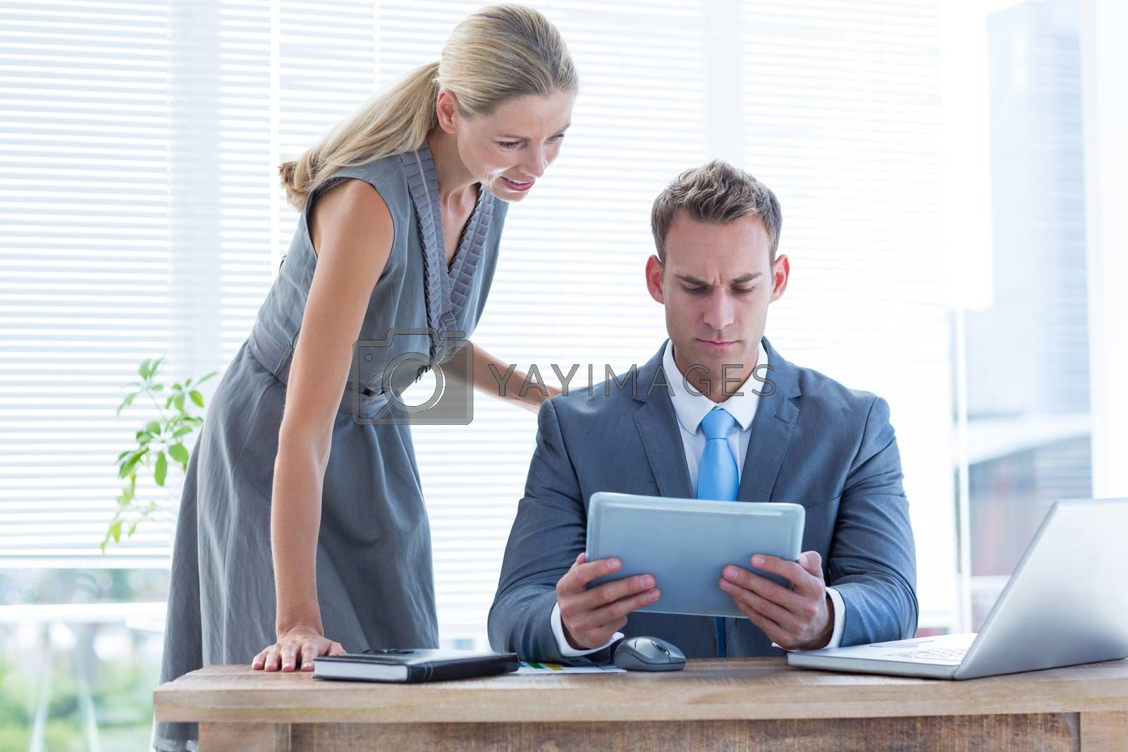 Royalty free image of Serious colleagues working together on tablet by Wavebreakmedia
