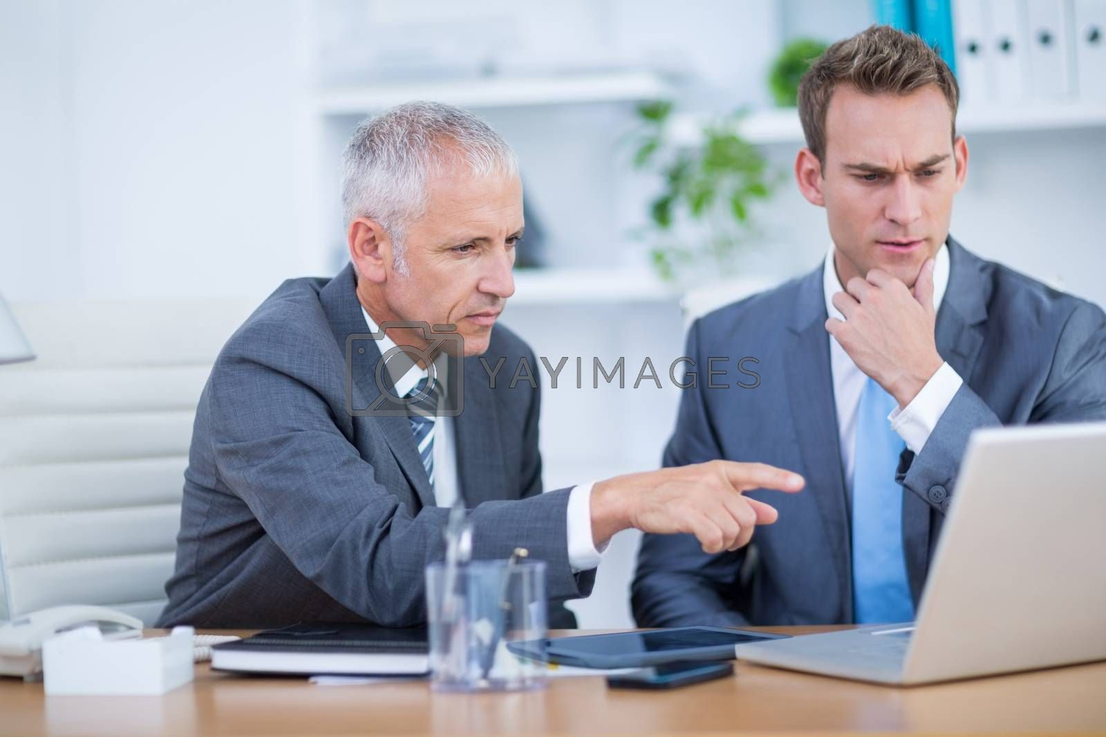 Royalty free image of Serious businessmen working together on laptop by Wavebreakmedia