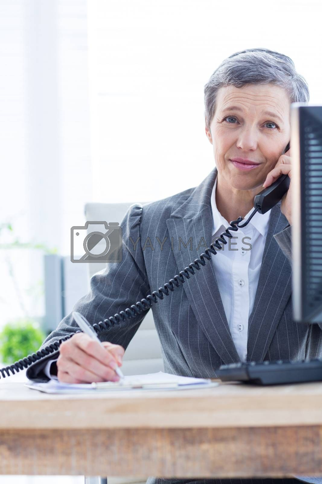 Royalty free image of Smiling portrait of a businesswoman phoning and writing by Wavebreakmedia