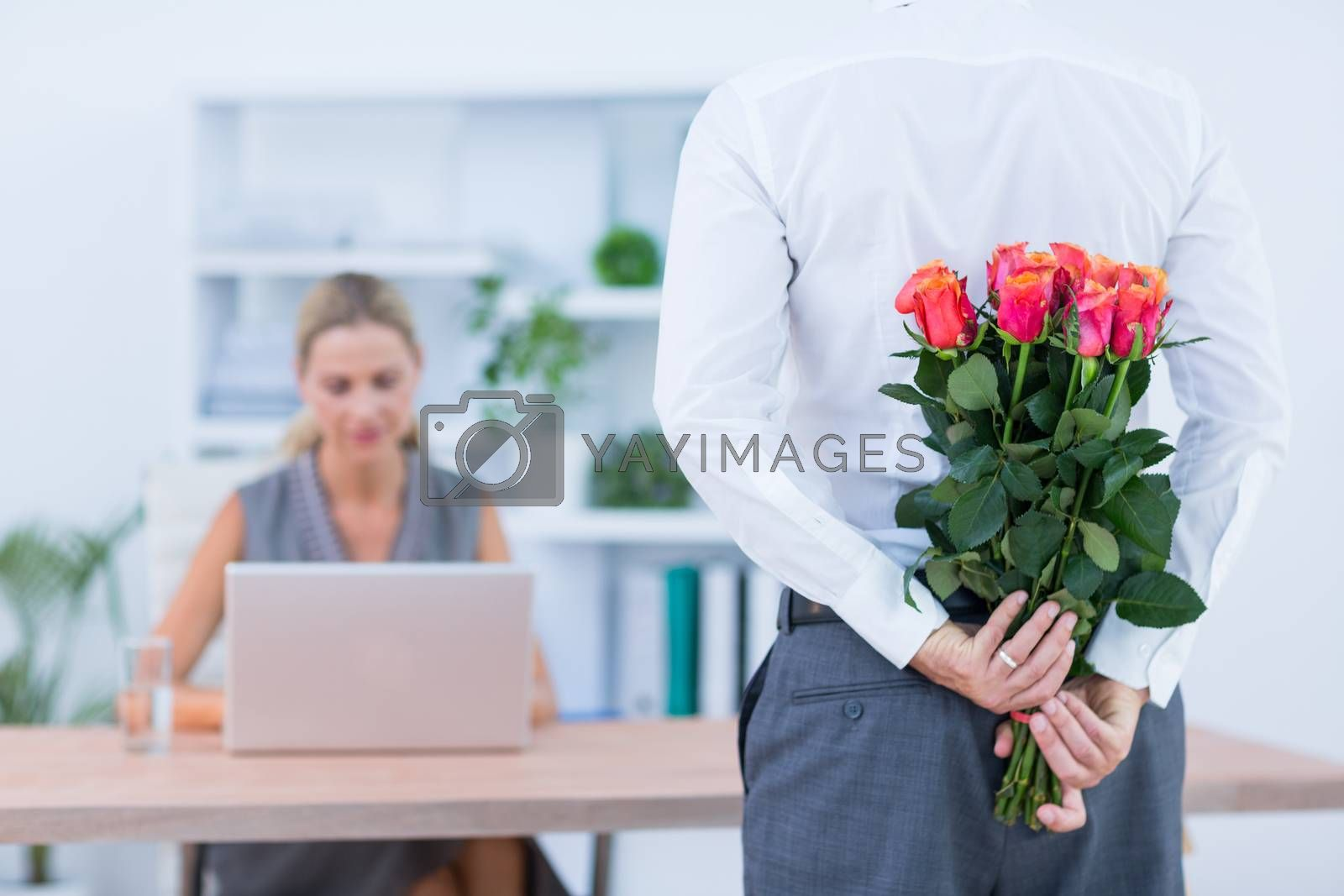 Royalty free image of Businessman hiding flowers behind back for colleague  by Wavebreakmedia