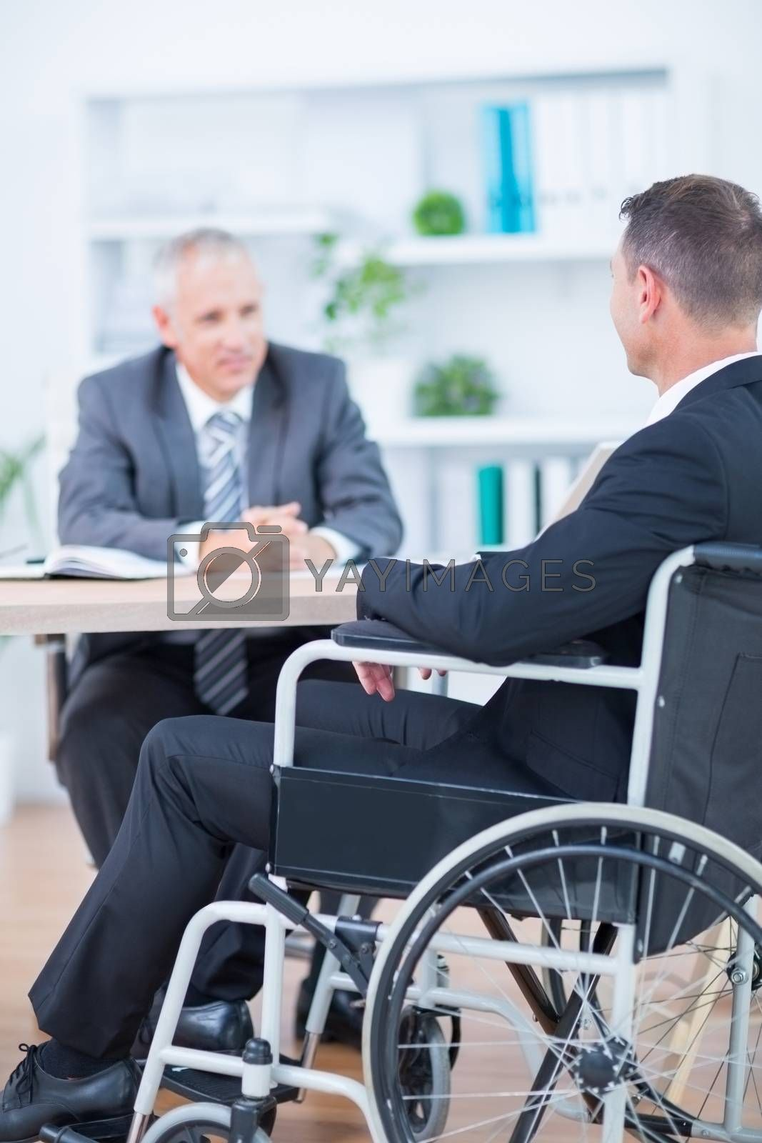 Royalty free image of Businessman in wheelchair speaking with colleague by Wavebreakmedia