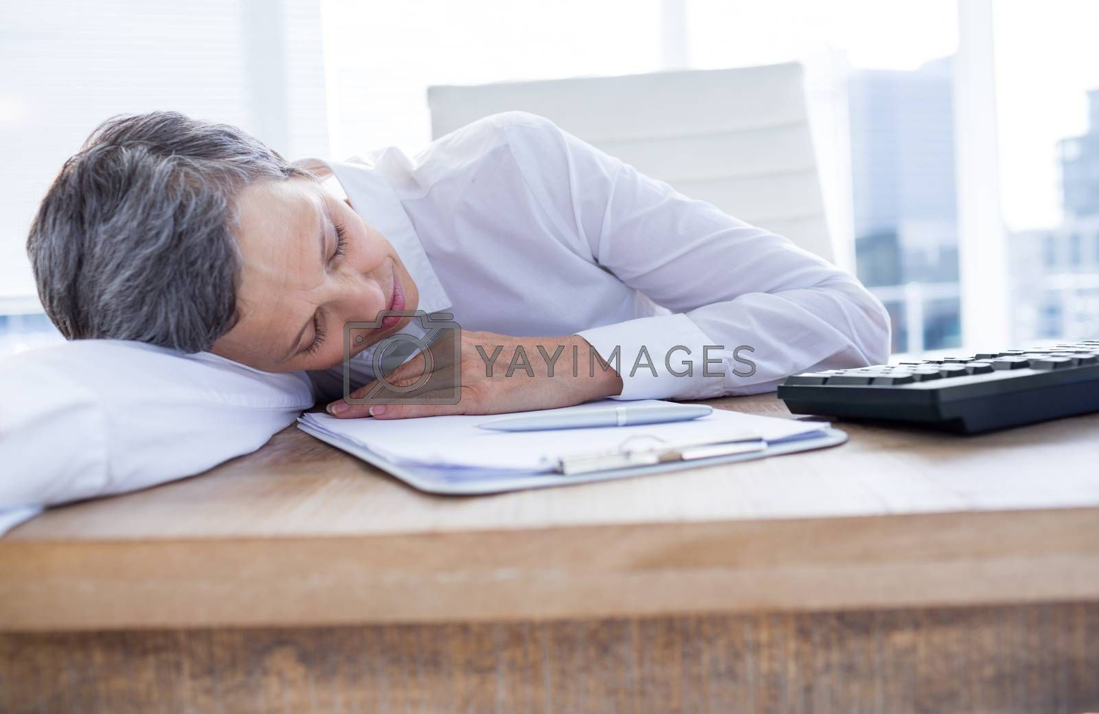 Royalty free image of Tired businesswoman sleeping at her desk by Wavebreakmedia