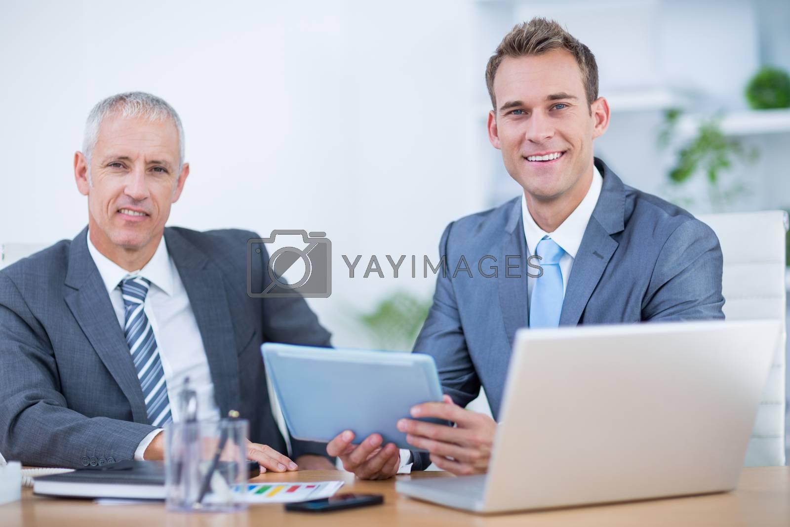 Royalty free image of Happy businessmen working together on digital tablet by Wavebreakmedia