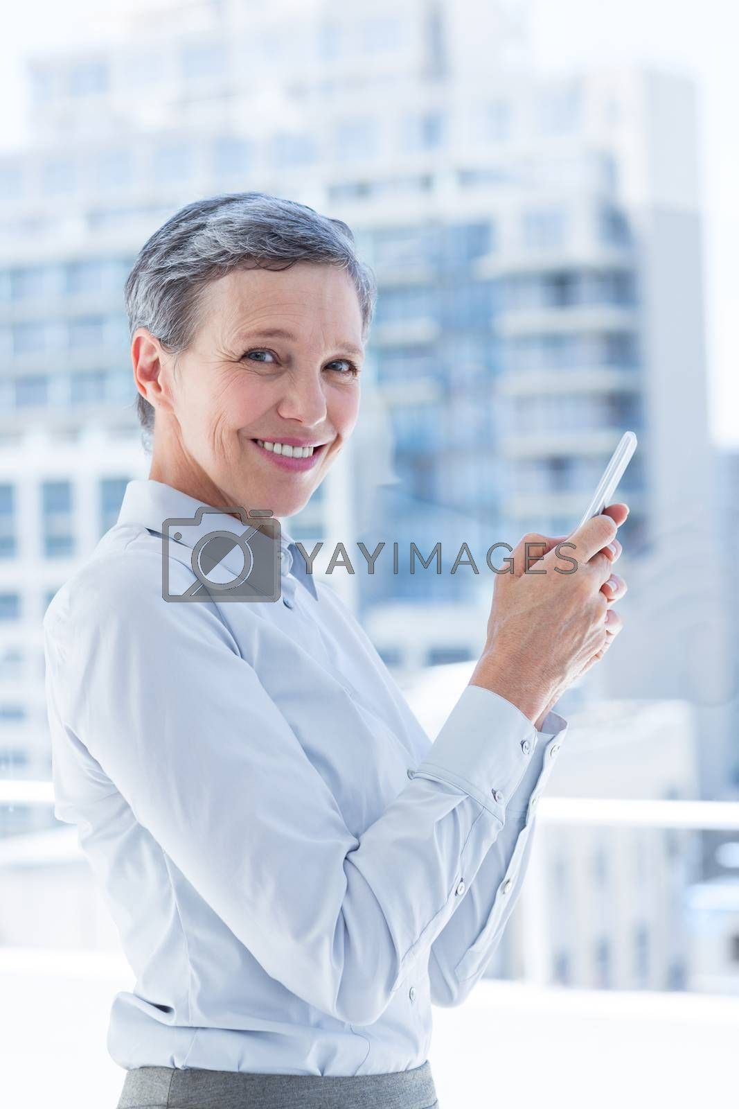 Royalty free image of Businesswoman sending a text message in the office by Wavebreakmedia