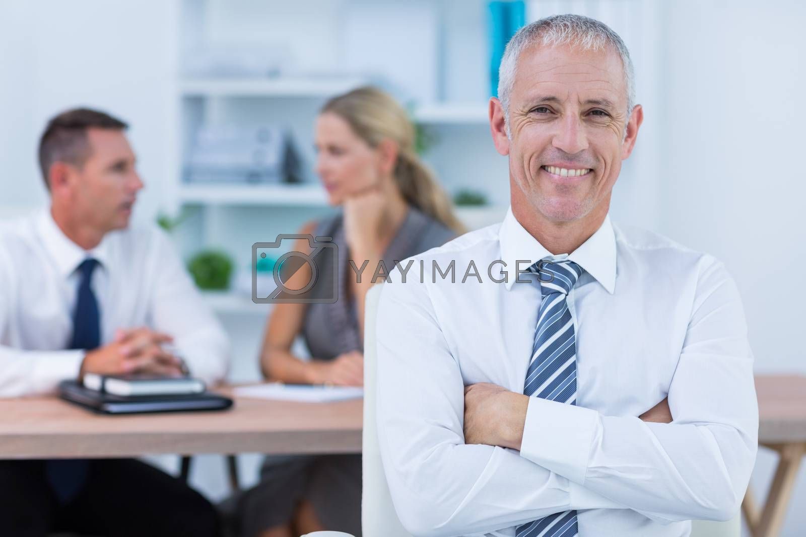 Royalty free image of Happy businessman smiling at camera with colleagues behind by Wavebreakmedia
