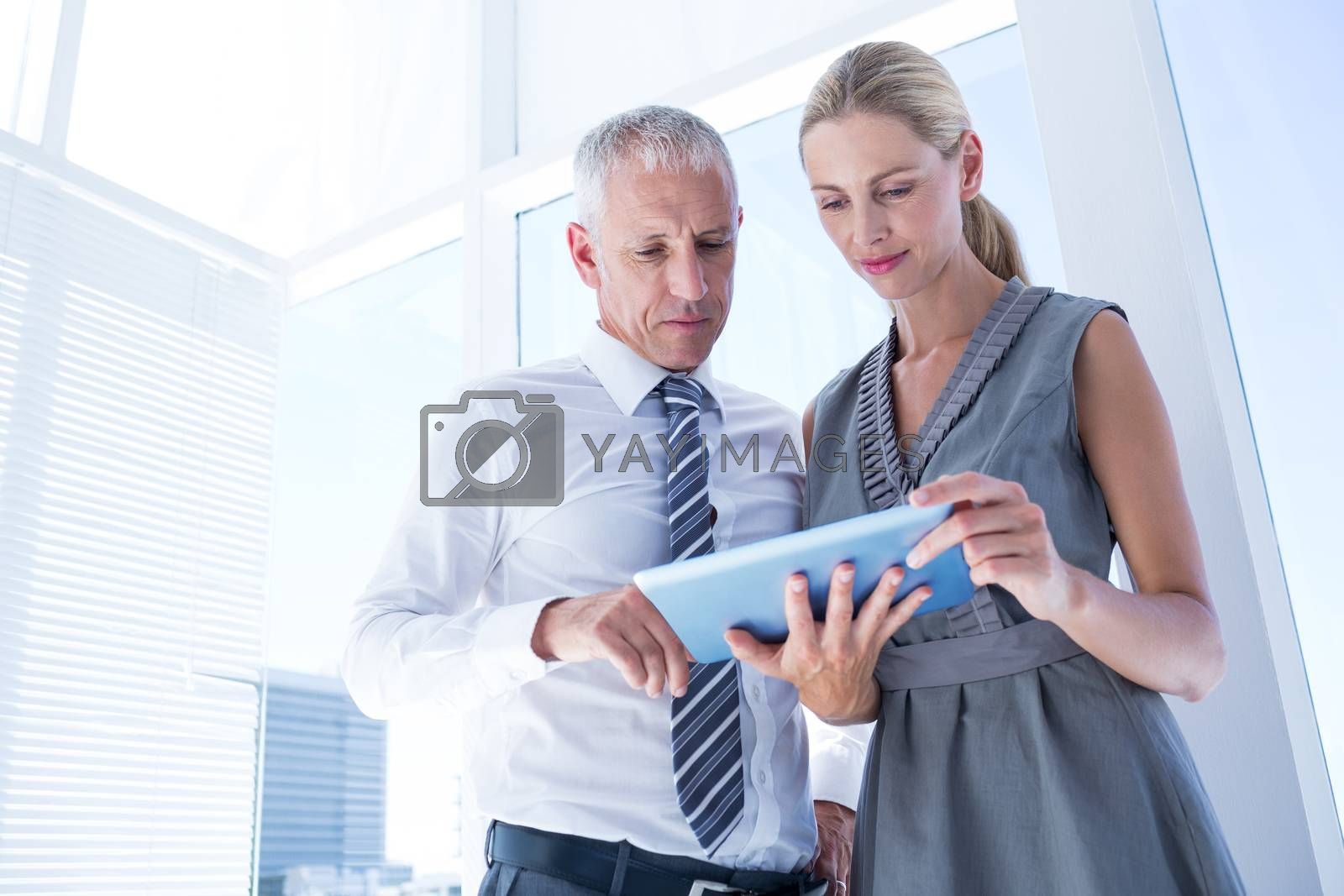 Royalty free image of Business people discussing over a digital tablet by Wavebreakmedia