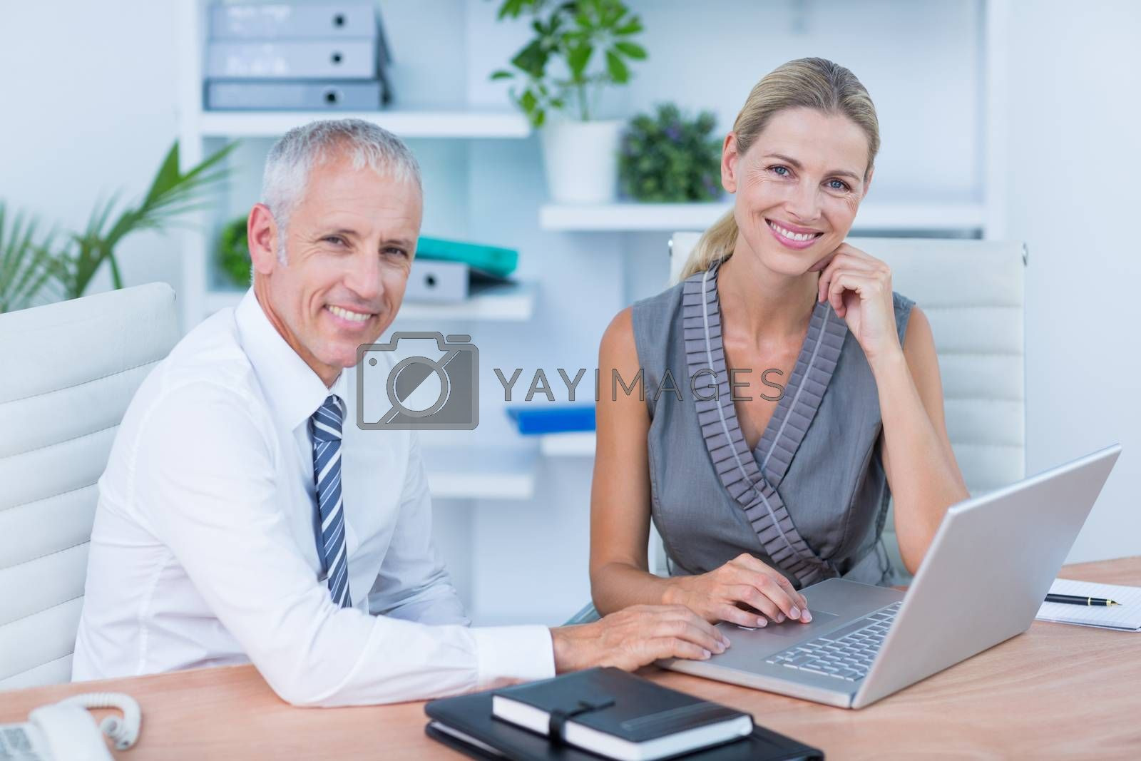 Royalty free image of Portrait of colleagues using laptop  by Wavebreakmedia