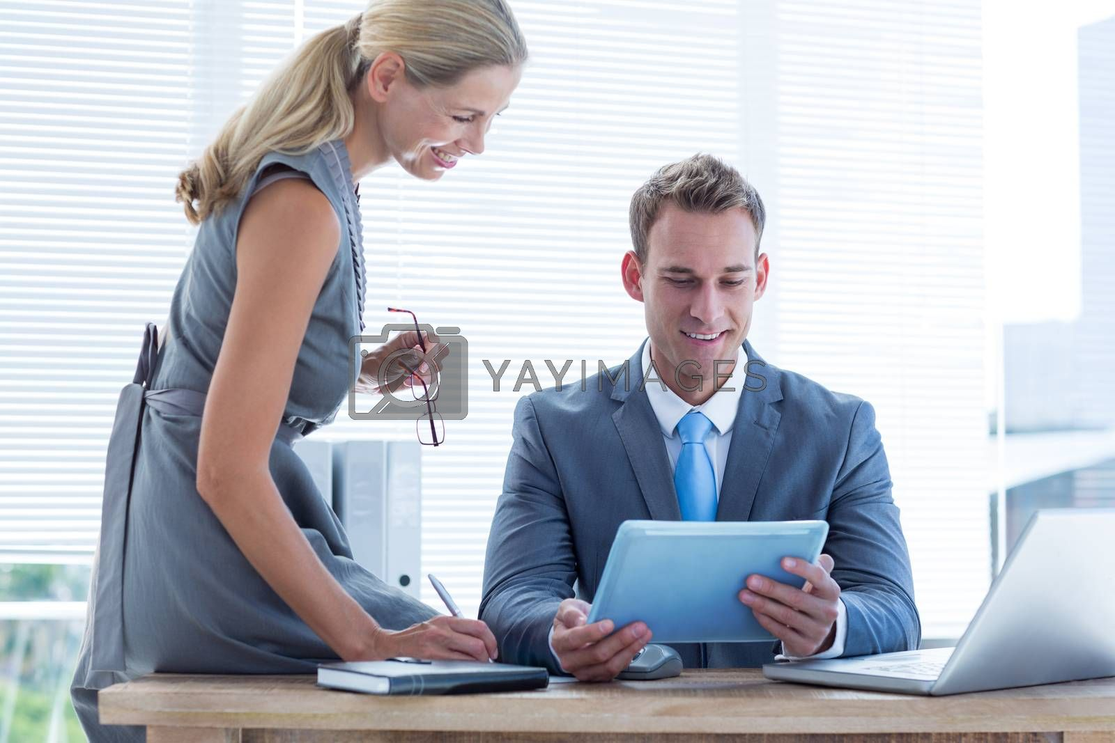 Royalty free image of Businessman with secretary looking at tablet by Wavebreakmedia
