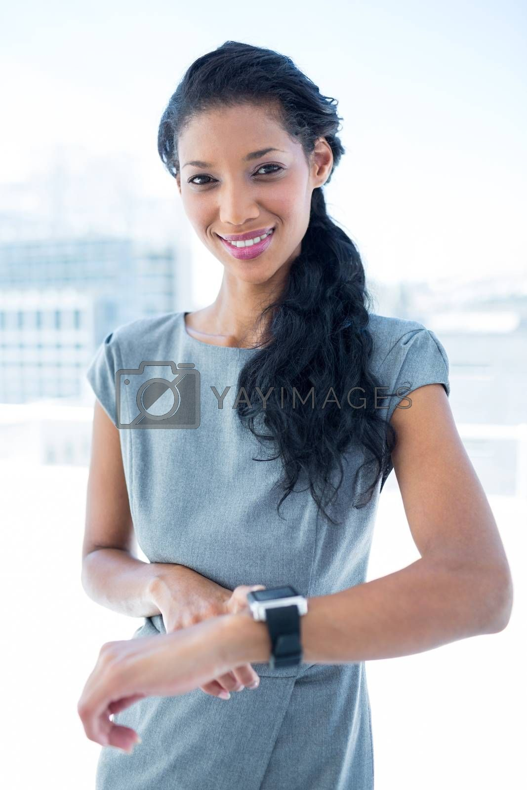 Royalty free image of Smiling businesswoman using her smartwatch by Wavebreakmedia