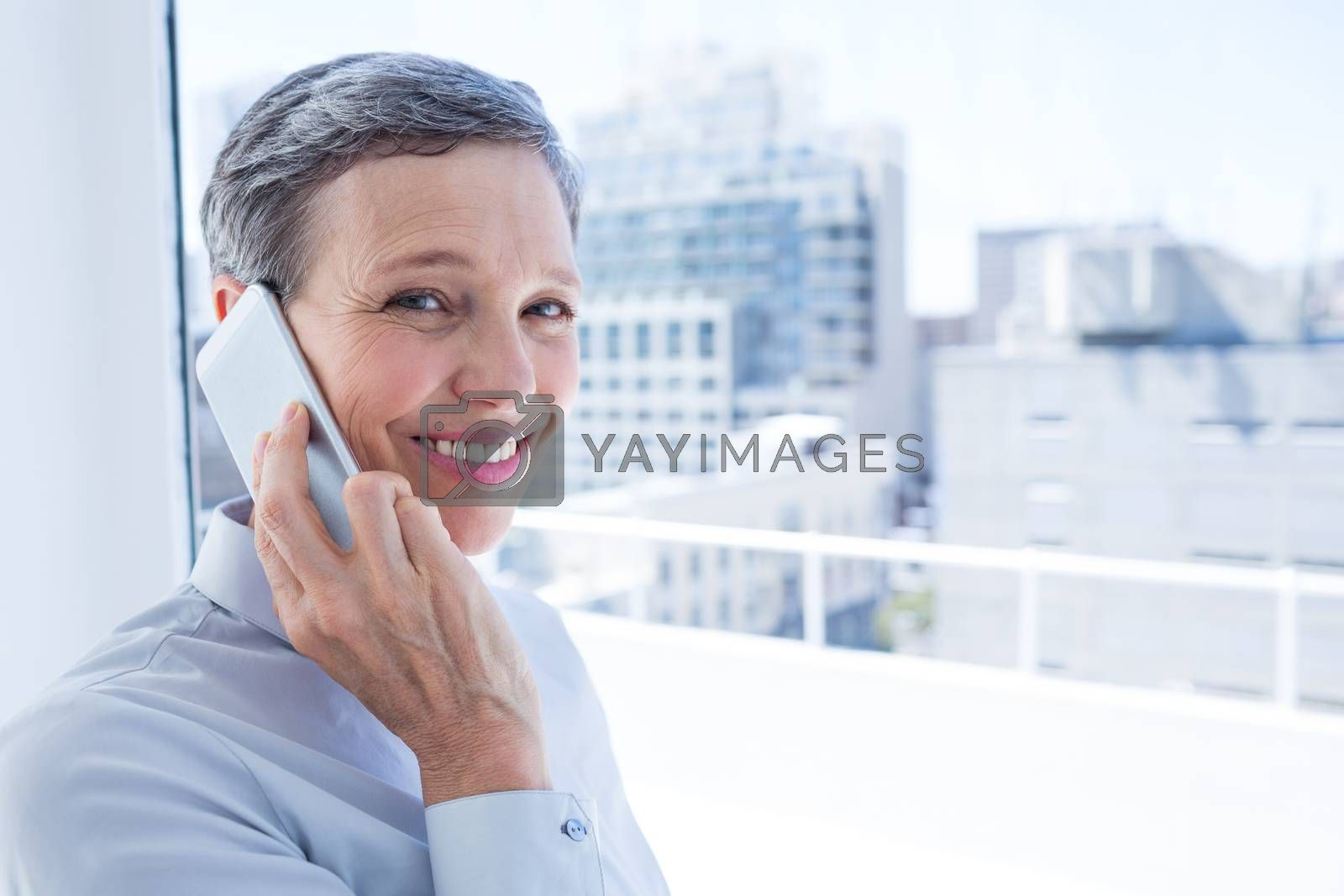 Royalty free image of Businesswoman looking at camera while on the phone by Wavebreakmedia