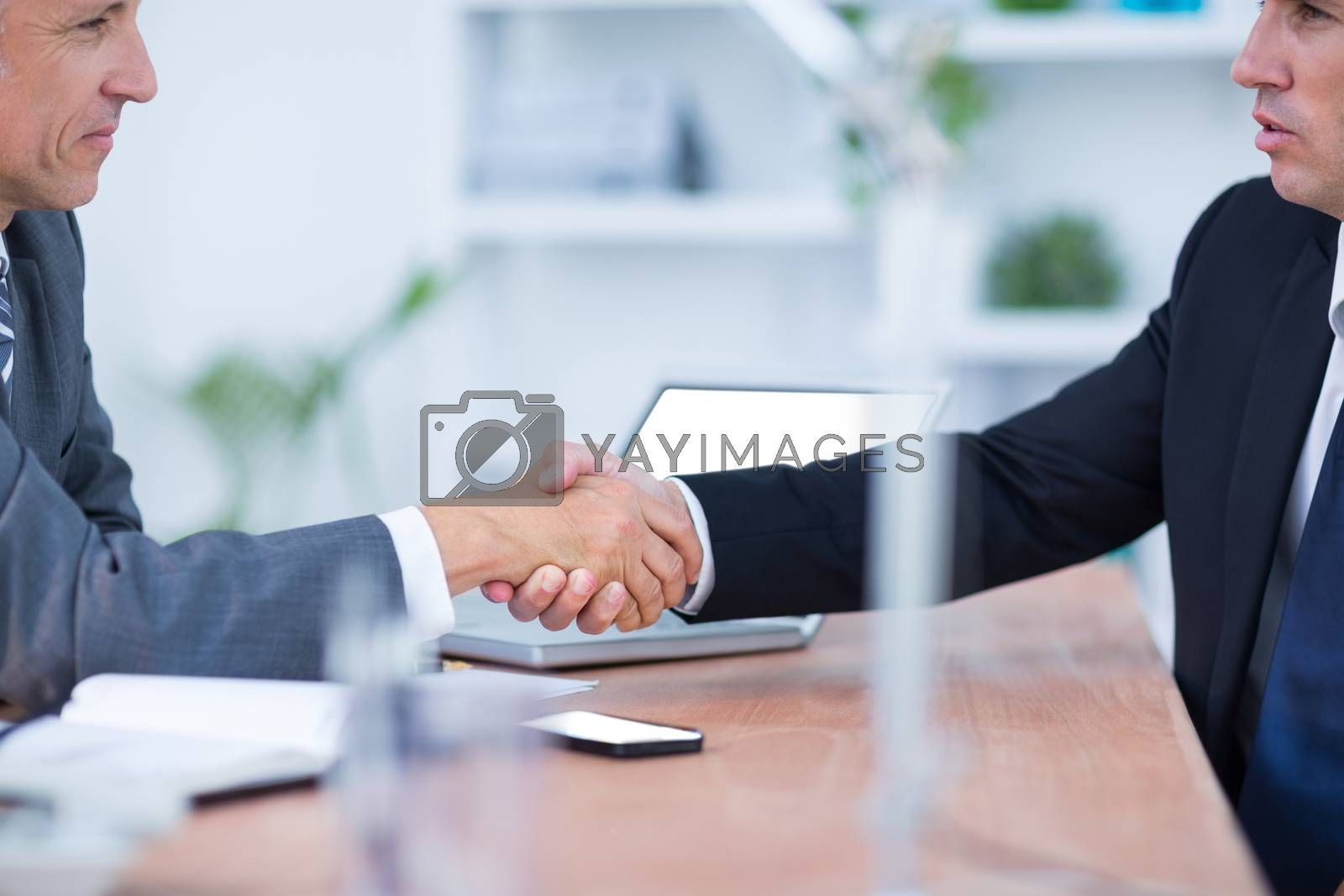 Royalty free image of Two businessmen shaking hands and working  by Wavebreakmedia