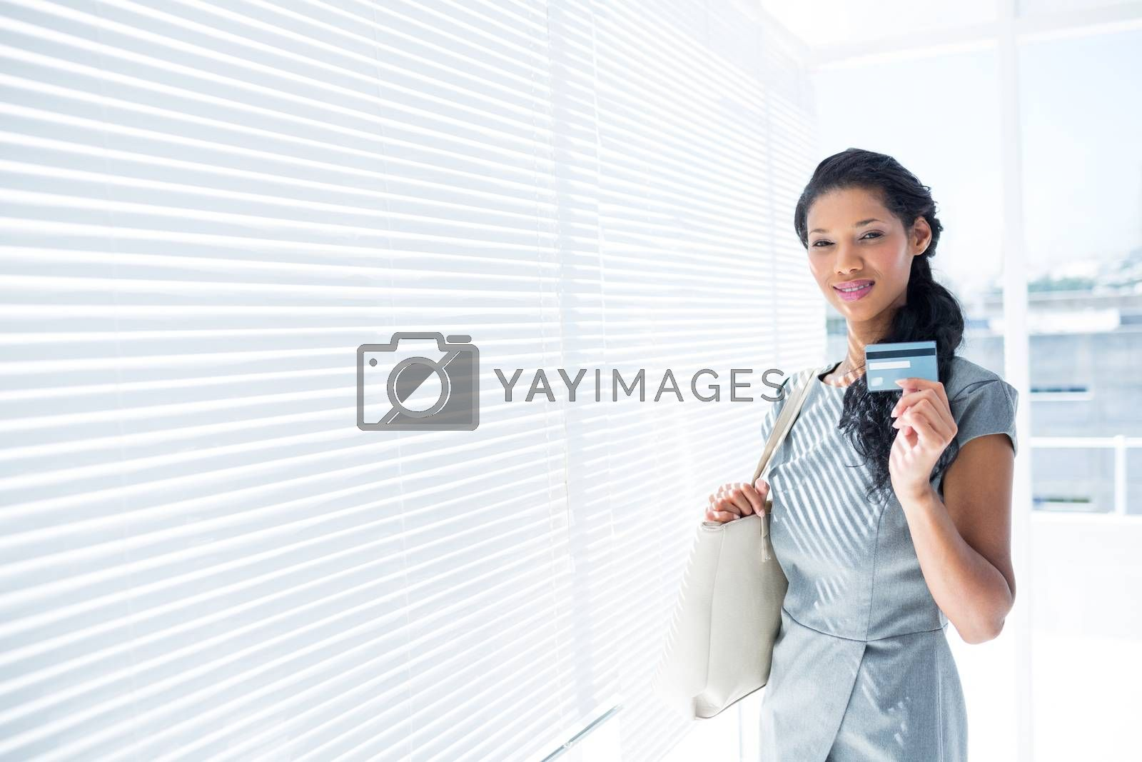 Royalty free image of Smiling businesswoman looking at camera with credit card by Wavebreakmedia