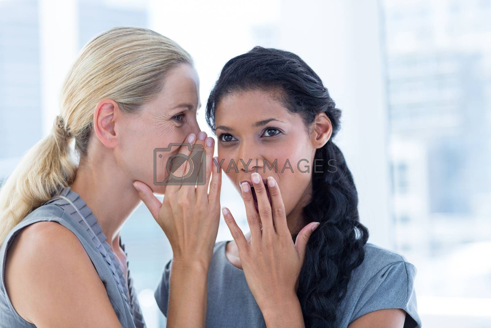 Royalty free image of Businesswoman whispering gossip to her colleague by Wavebreakmedia