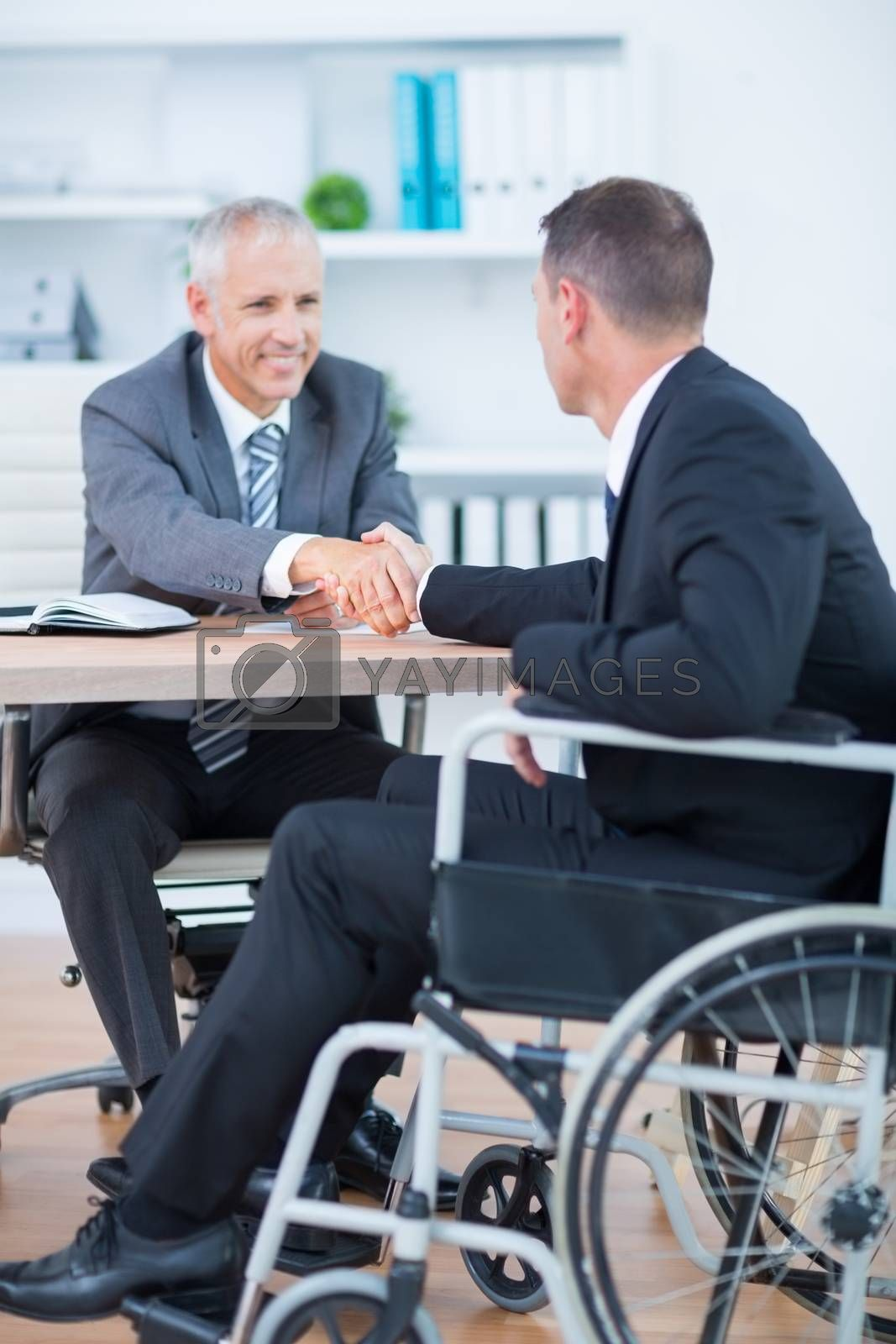 Royalty free image of Businessman in wheelchair shaking hands with colleague by Wavebreakmedia