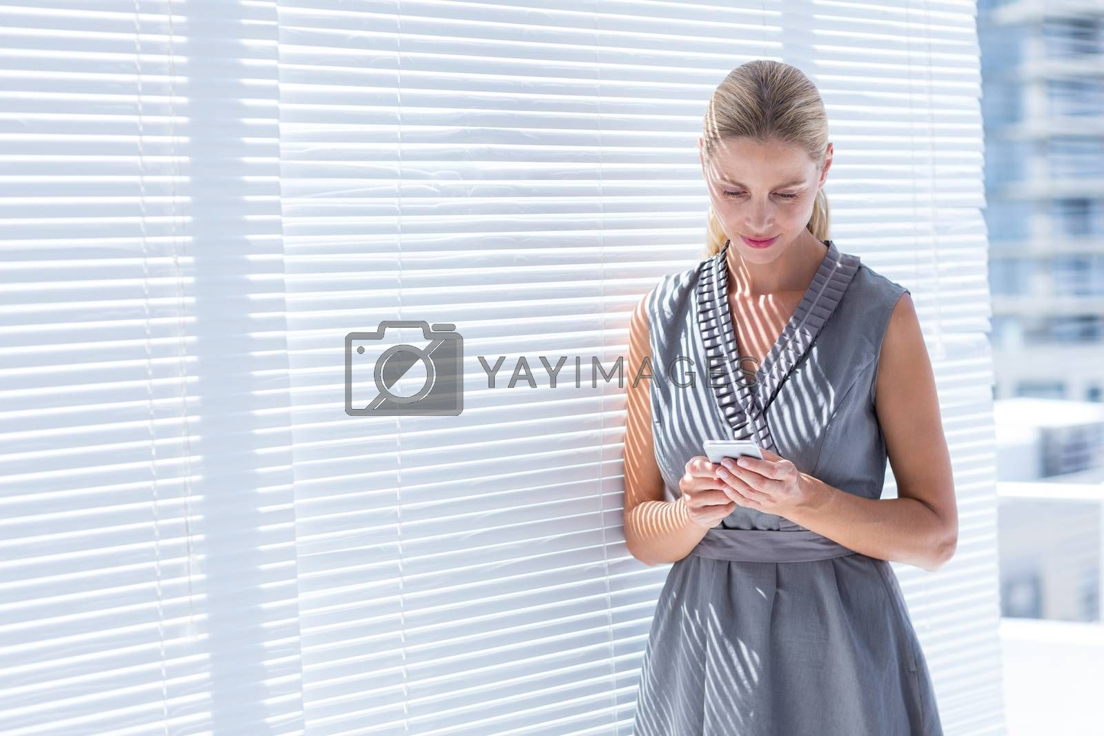Royalty free image of Concentrated businesswoman sending a text message by Wavebreakmedia