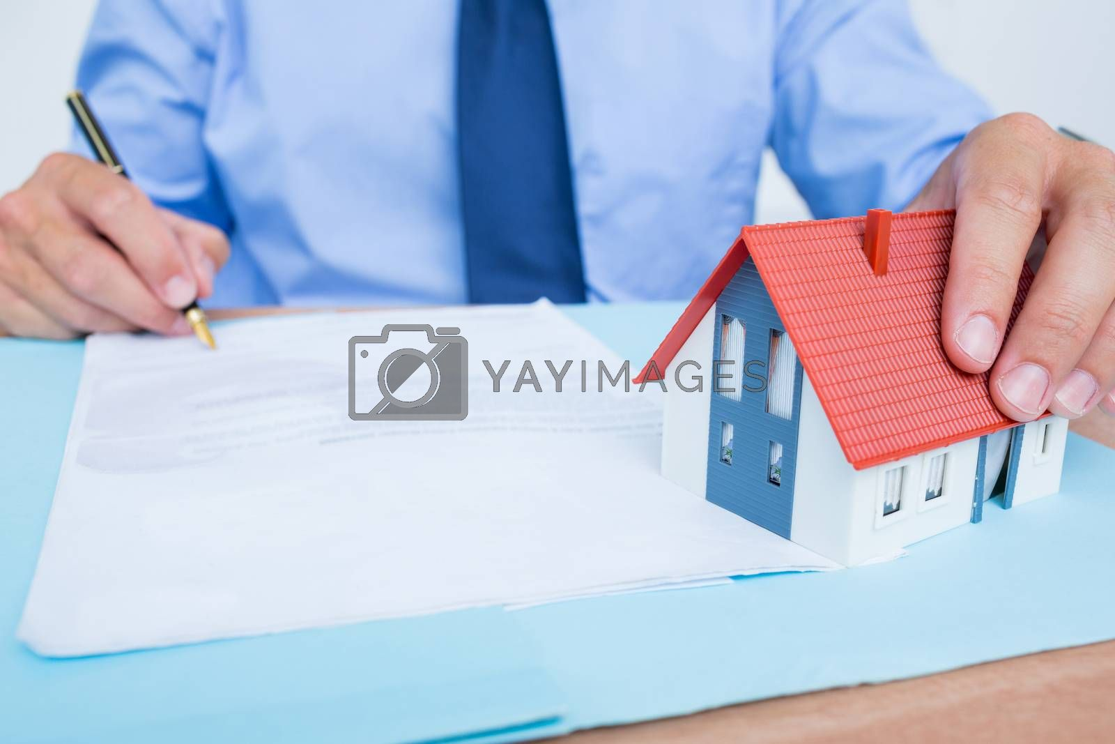 Royalty free image of Businessman reading and writing a contrat before signing it by Wavebreakmedia