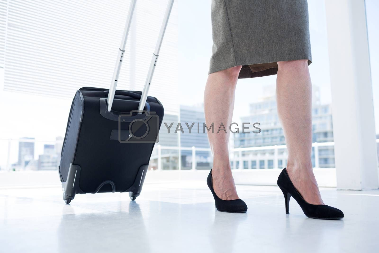 Royalty free image of Businesswoman pulling her suitcase in the office by Wavebreakmedia