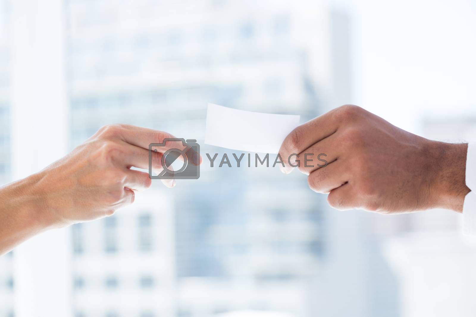 Royalty free image of Hands giving small paper sheet to another one by Wavebreakmedia