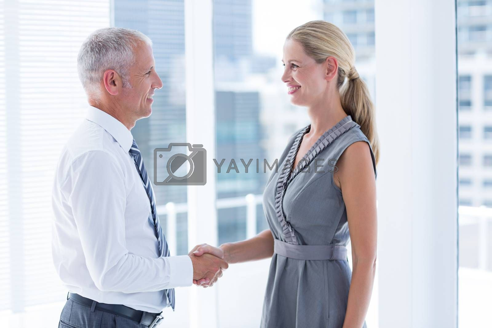 Royalty free image of Two smiling business people shaking hands by Wavebreakmedia