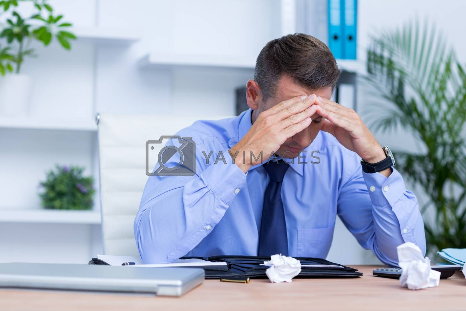 Royalty free image of Businessman with severe headache sitting at office desk by Wavebreakmedia